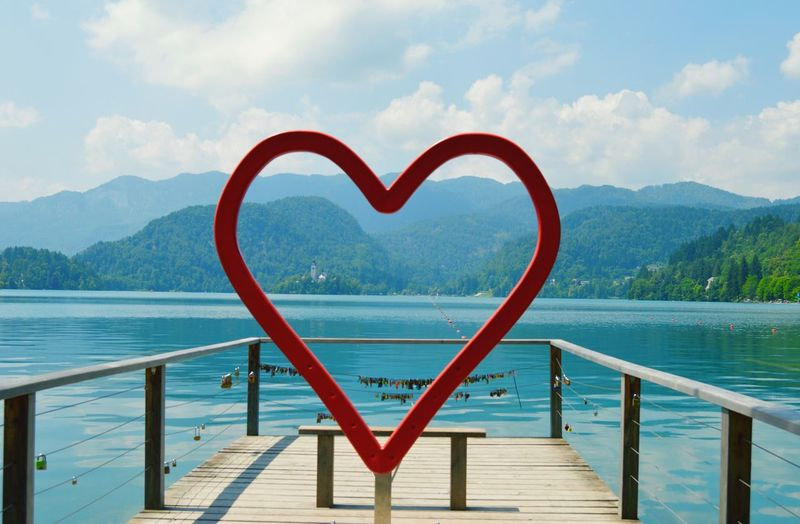 I fell in love with this country on the first day ❤️ the beautiful Lake Bled in Slovenia Heart Shape Water Love Red Sky Day Scenics No People Mountain Tranquility Nature Tranquil Scene Cloud - Sky Outdoors Wood - Material Beauty In Nature Lake Close-up Slovenia Lake View