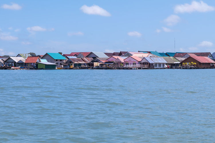 Houses by sea against blue sky