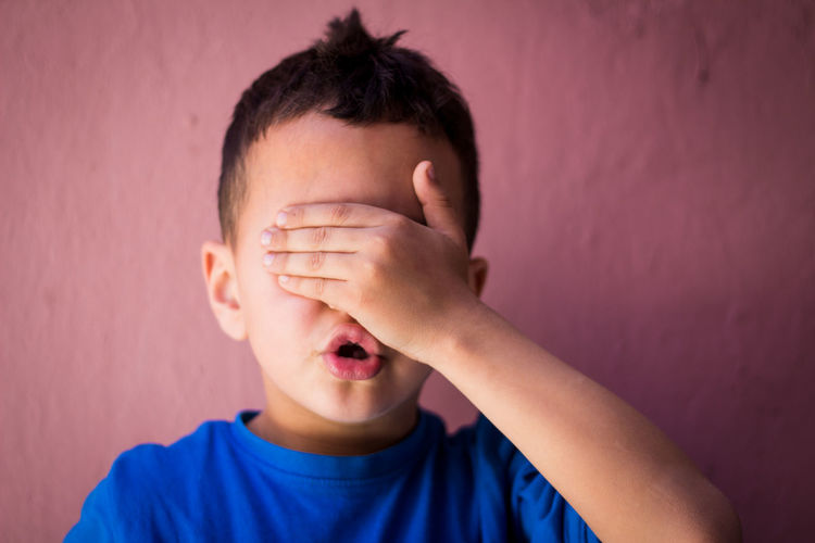 Close-up of boy with hands covering eyes against wall