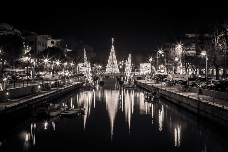 Scenic view of the Christmas Tree on a bridge at night in black and white. Long exposure picture in Riccione, Emilia Romagna, Italy. Riccione Christmas New Year Around The World New Year Decoration Celebration Ice Carpet Port Harbor Emiliaromagna Italy Long Exposure Water Reflection Waterfront Long Exposure Shot Sunset Cloud - Sky Nautical Vessel Sailboat No People Night Illuminated Architecture Transportation Mode Of Transportation Built Structure Building Exterior River Bridge Moored City Travel Destinations Nightlife