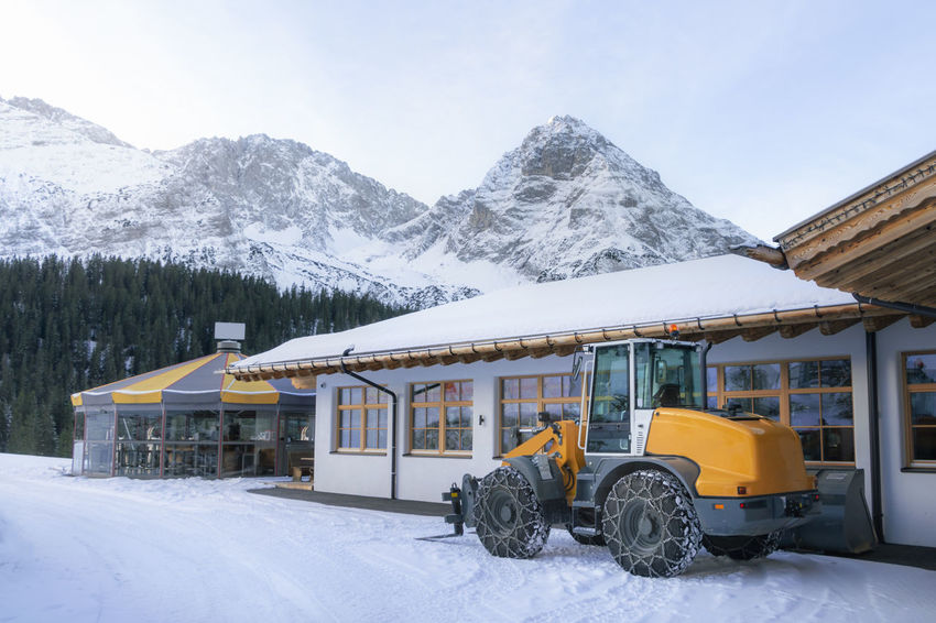 Wheel loader with chains on its tires, for plowing snow, in winter alpine scenery, the snow-capped Alps, a ski resort, in Ehrwald, Austria. Snow Winter Cold Temperature Mountain Architecture Built Structure Transportation Mode Of Transportation Snowcapped Mountain Building Land Vehicle Nature Mountain Range No People Outdoors Wheel Loader Buldozer Snow Machine Machinery Austria Austrian Alps