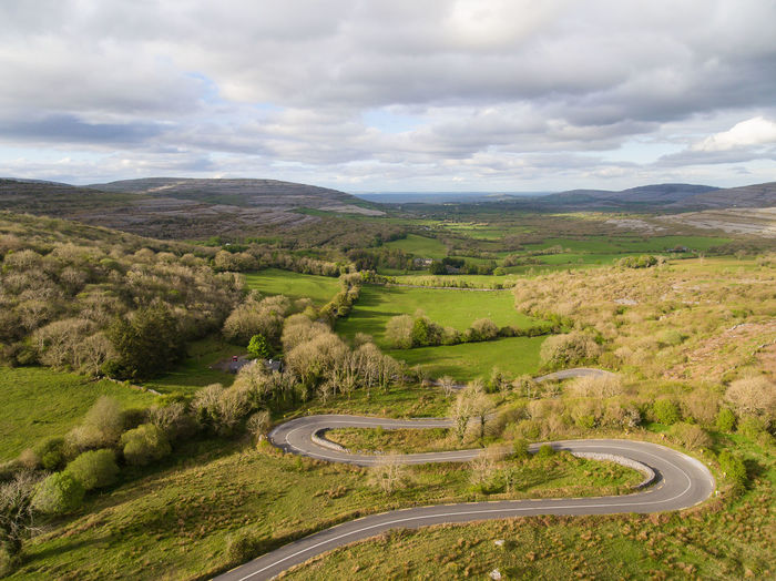 High angle view of winding road on landscape against sky