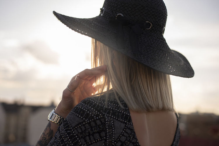 Close-up portrait of woman wearing hat against sky