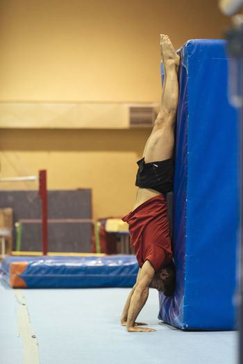 Side view of young man exercising at gym