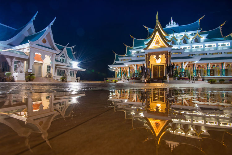 Illuminated temples reflecting on water at night