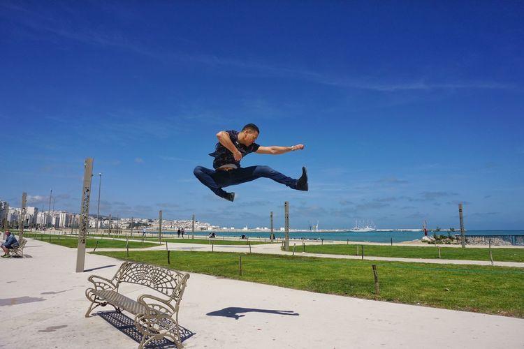 Full Length Of Man Jumping At Park Against Blue Sky