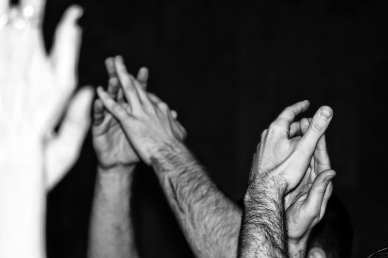 Cropped hands of people clapping against black background