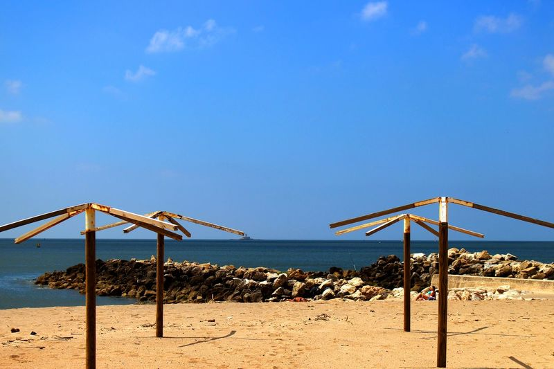 Scenic view of emoty beach umbrellas and sea against blue sky