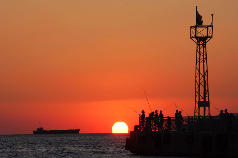 Silhouette ship in sea against orange sky