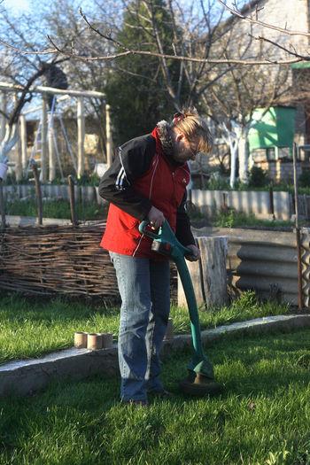 Woman using gardening equipment while standing in yard