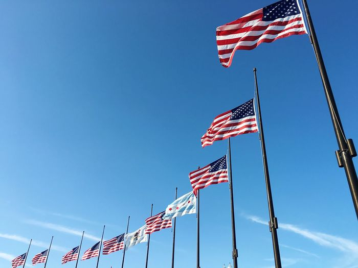 Low angle view of flags against blue sky