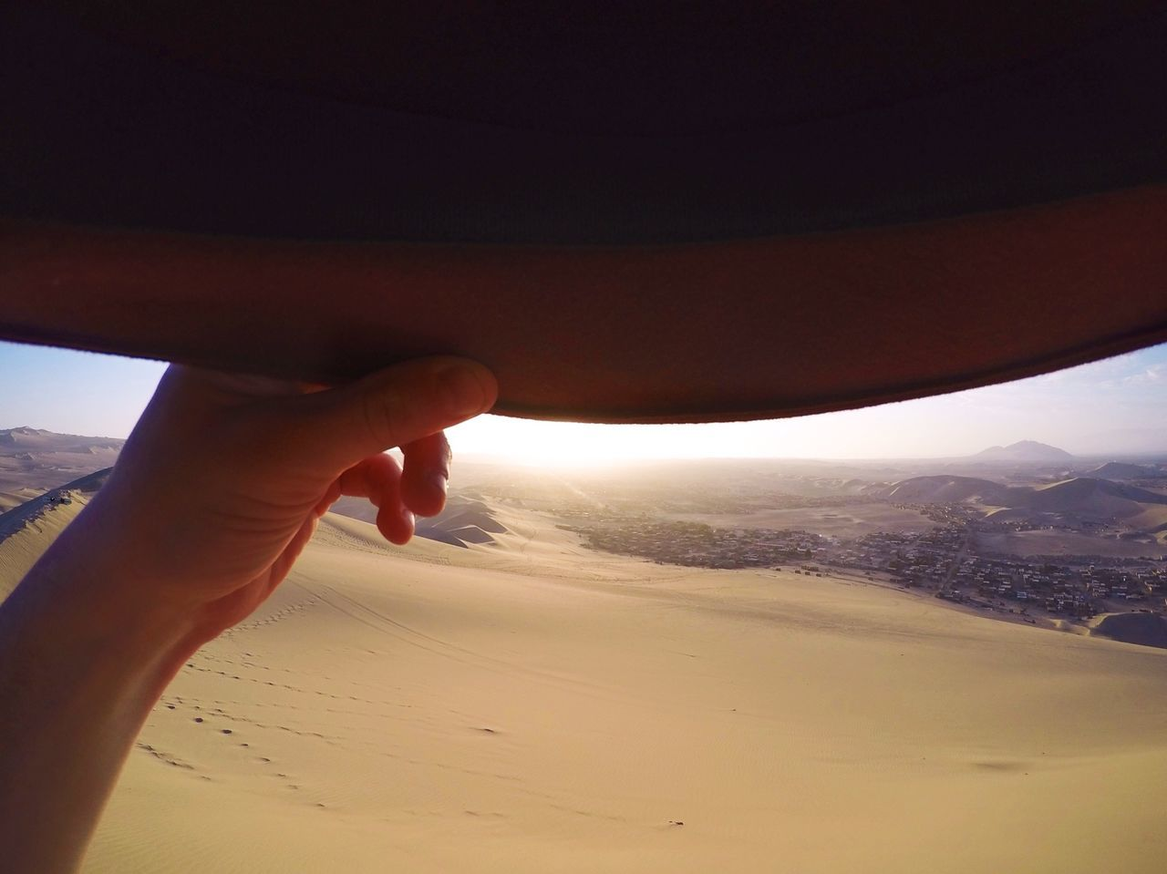 Close-Up Of Hand Holding Hat At Desert