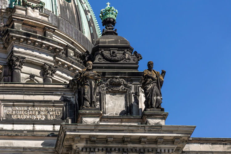 A close-up exterior view on a sculptural composition on the roof of Dom Berliner, also known as the Berlin Cathedral in the historic city of Berlin in Germany. Sculpture Representation Statue Human Representation Art And Craft Architecture Male Likeness Built Structure Creativity Low Angle View History The Past Craft Travel Destinations Day Building Exterior Clear Sky Memorial Outdoors Ornate Cathedral Dom Berlin Berlin Cathedral