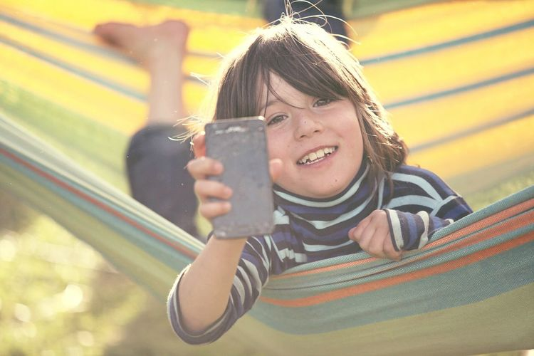 Leisure Activity Smiling One Person Photography Themes Happiness Sunlight Outdoors Childhood Technology Mobile Phone Broken Phone Child Hammock EyeEmNewHere Mobile Conversations The Portraitist - 2017 EyeEm Awards Be. Ready. Springtime Decadence