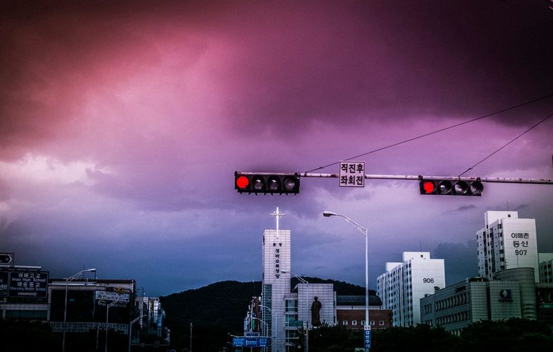 Road signals and buildings against cloudy sky at dusk