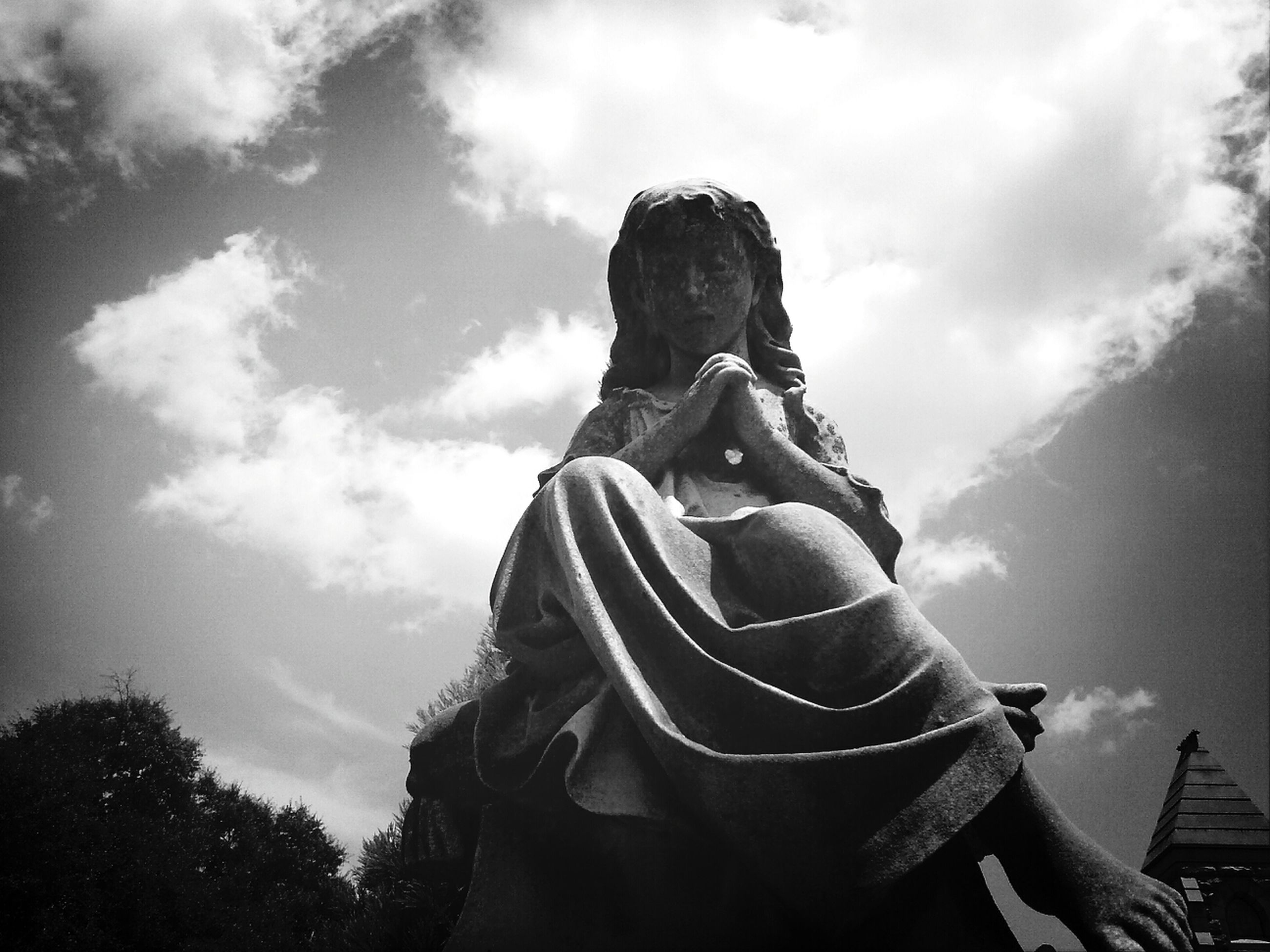 sky, low angle view, statue, sculpture, human representation, art, art and craft, creativity, cloud - sky, cloud, religion, spirituality, cloudy, outdoors, lifestyles, built structure