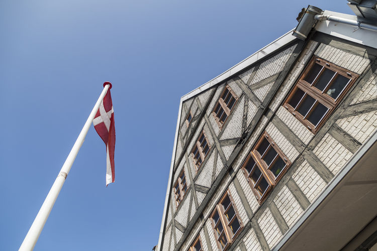 Dannebrog in the wind in front of a timber-framed house Low Angle View Sky Built Structure Architecture Building Exterior Flag Building No People Window Patriotism Nature Day Blue Clear Sky Outdoors Sunlight House Residential District Red Danmark Dannebrog Flags In The Wind