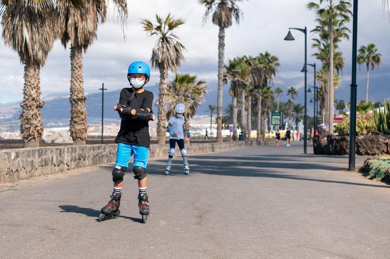 Full length of siblings wearing mask inline skating on road against sky