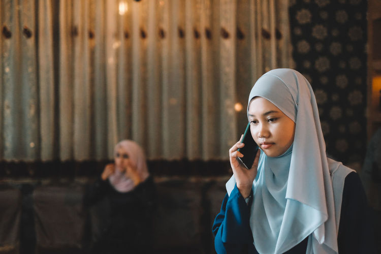 Young woman wearing hijab while answering mobile phone in city