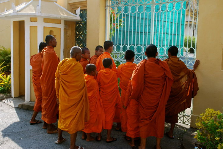 Rear view of monks standing in front of closed gate