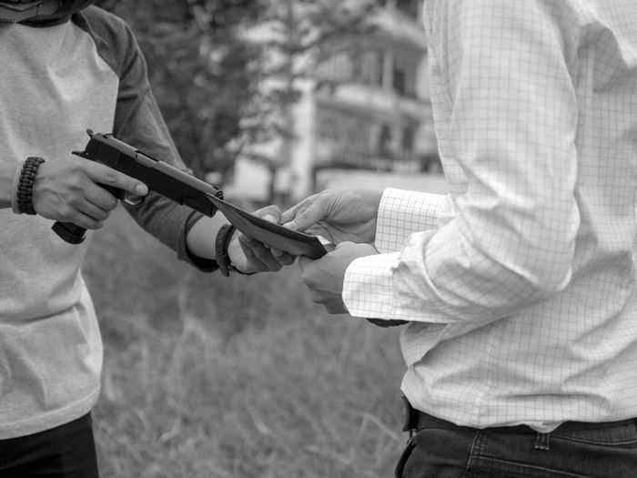 Midsection of burglar aiming gun on man