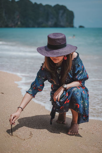 Drawing a heart Beach Hat Water Land Sea Leisure Activity Real People One Person Lifestyles Full Length Clothing Women Casual Clothing Sand Nature Day Vacations Holiday Outdoors Drawing Wave Krabi Thailand Krabi Heart
