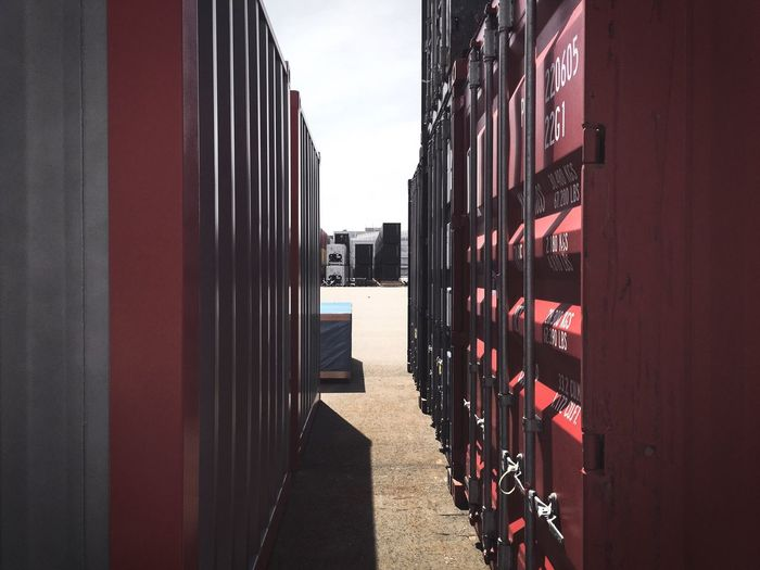 Cargo containers at dock against clear sky