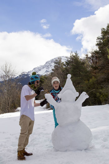 Young boy and girl make a snowman on a sunny day in the winter snow-covered forest in the mountains. Positive Emotion Warm Clothing Outdoors Tree Snowball Togetherness Full Length Cloud - Sky Mountain Two People Leisure Activity Day Sky Snowman Nature Cold Temperature Winter Snow Couple Winter Time Brother & Sister Sunny Day Weekend Holiday Joy Winter Family Smiling Happiness Nature