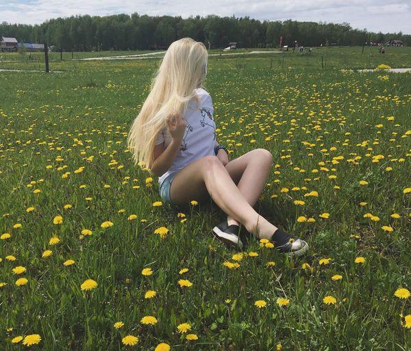 Rear view of woman sitting on field