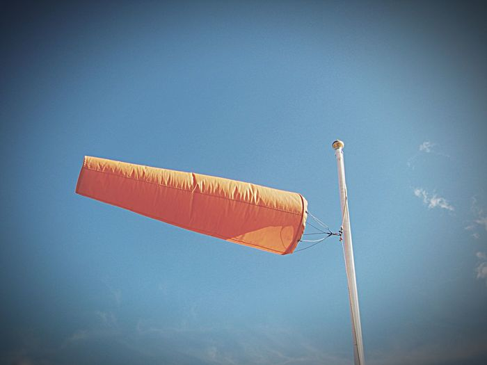 Low Angle View Of Windsocks Blowing In Wind Against Sky