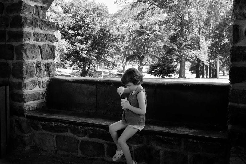 Girl on seat holding yogurt against trees