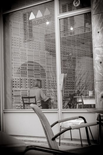 Reflection of man sitting in glass window