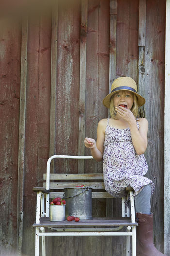 Girl wearing hat standing against wall
