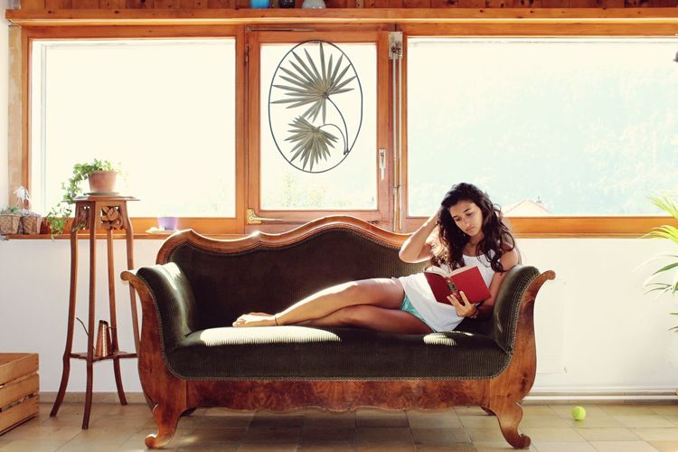 Woman sitting on sofa at home