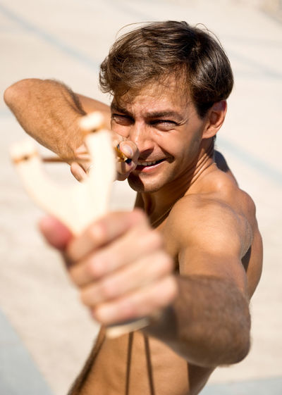 Shirtless man aiming with slingshot
