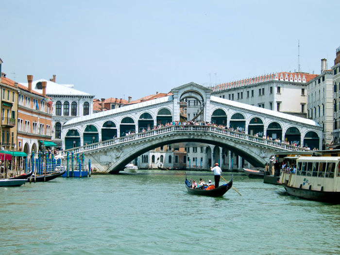 Canal Grande Rialto Bridge Architecture Bridge - Man Made Structure Building Exterior Built Structure Canal Clear Sky Connection Day Gondola Gondola - Traditional Boat Gondolier Large Group Of People Men Mode Of Transport Nautical Vessel Outdoors People Real People Tourism Transportation Travel Destinations Water