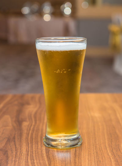 Refreshment Drink Alcohol Beer - Alcohol Glass Food And Drink Beer Table Drinking Glass Beer Glass Household Equipment Wood - Material Focus On Foreground Freshness Still Life No People Close-up Glass - Material Bar - Drink Establishment Indoors  Frothy Drink Pint Glass Bar Counter