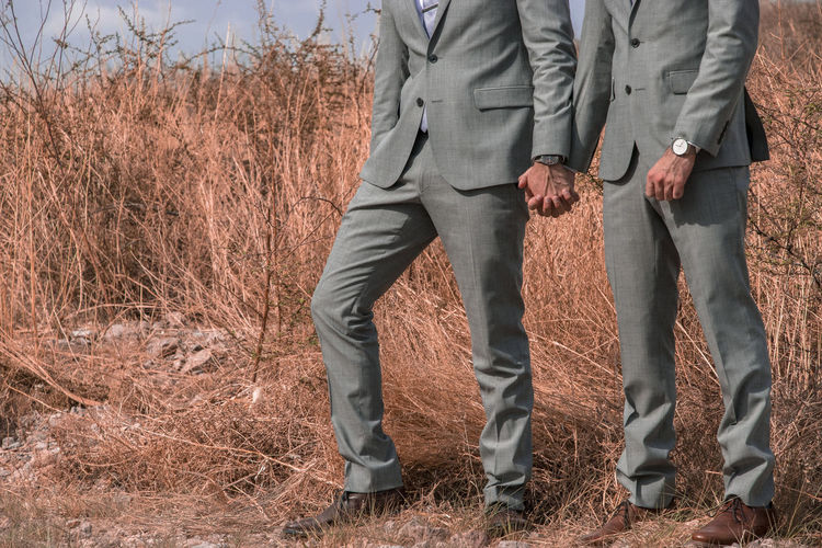 Low Section Of Gay Couple Wearing Suit Standing On Field
