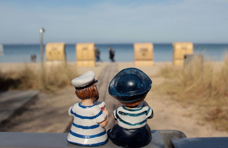 Sailors figurine on retaining wall at beach