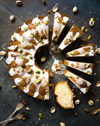 lemon pistachio cake cutted in slices on a dark backdrop | daylight foodphotography Cake Lemon Cake Pistachio Baked Foodphotography Food Photography Dessert Slices Dark Mood From Above  High Angle View Fork Light And Shadow No People Tasty Delicious Frosting Vegetarian Food