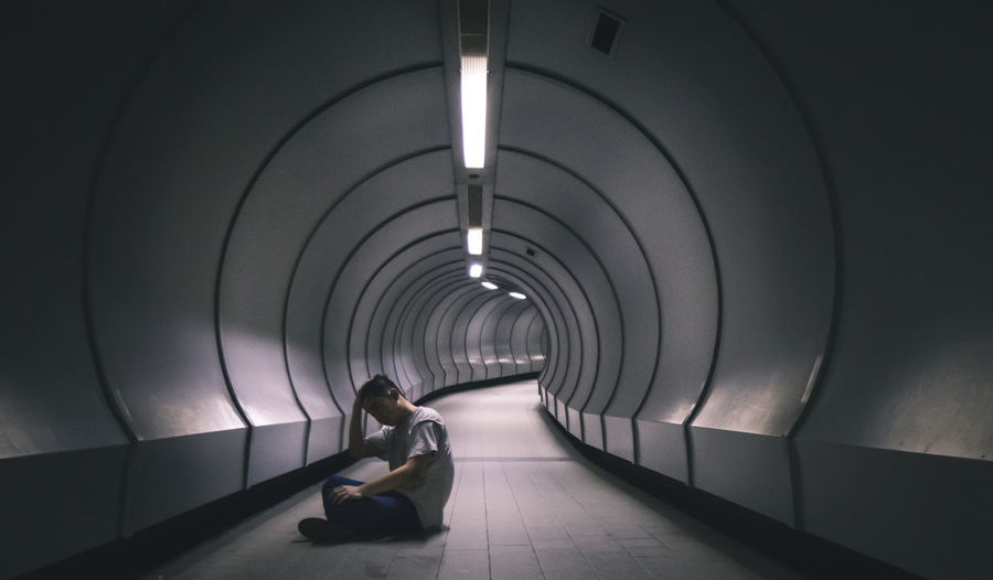 Woman sitting in tunnel