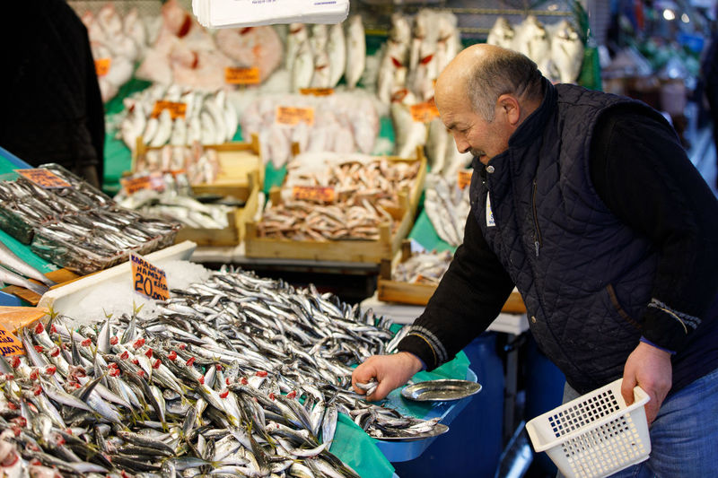 Market FishMarket Turkey Istanbul Fish Retail  Men One Person Adult Business Side View Food And Drink Males  Food Seafood Waist Up Large Group Of Objects Choice Freshness Holding Market Stall Mature Men Fishing Industry Buying Consumerism