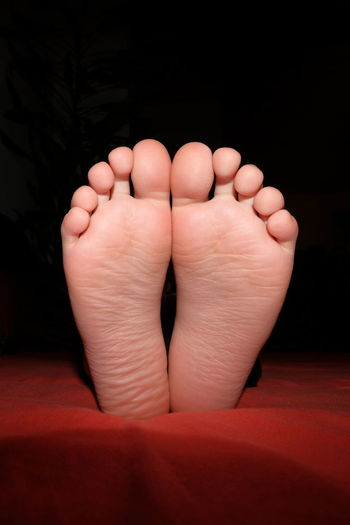 close up of two foot soles Body Part Human Body Part Indoors  One Person Foot Feet barefoot Black Background Close-up Close Up Closeup Human Foot Relaxation Sole Of Foot Low Section Real People Human Toe Human Limb Vertical