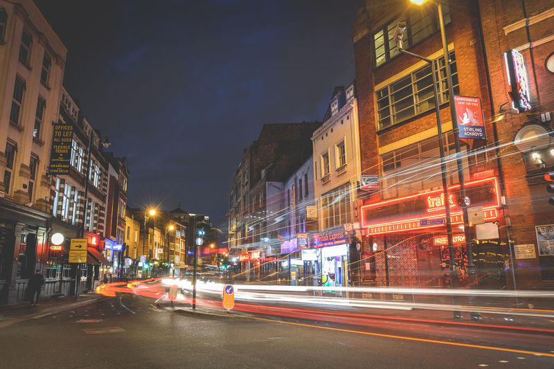 Light trails on city street by buildings at night