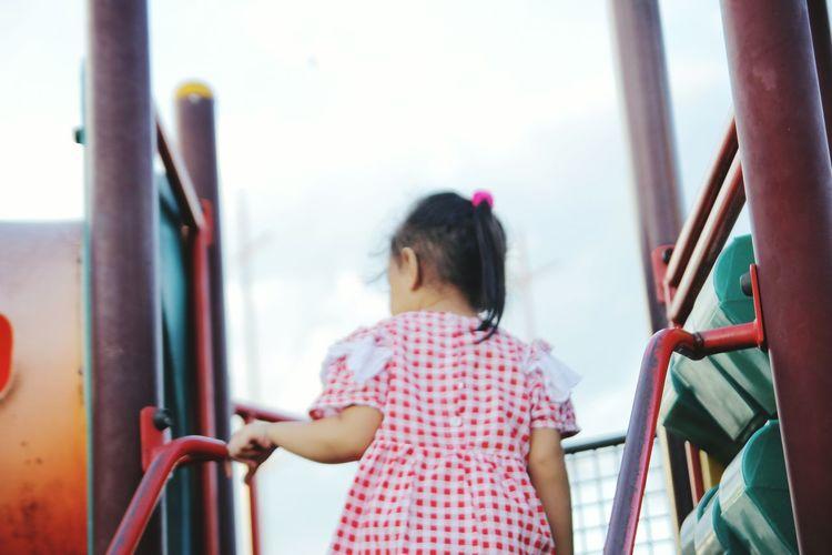 Rear View Of Girl Standing On Slide
