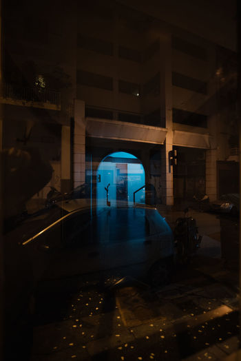 Car seen through window by building at night