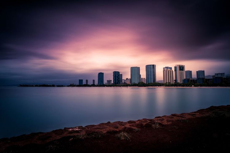 Sea and buildings against cloudy sky during sunset