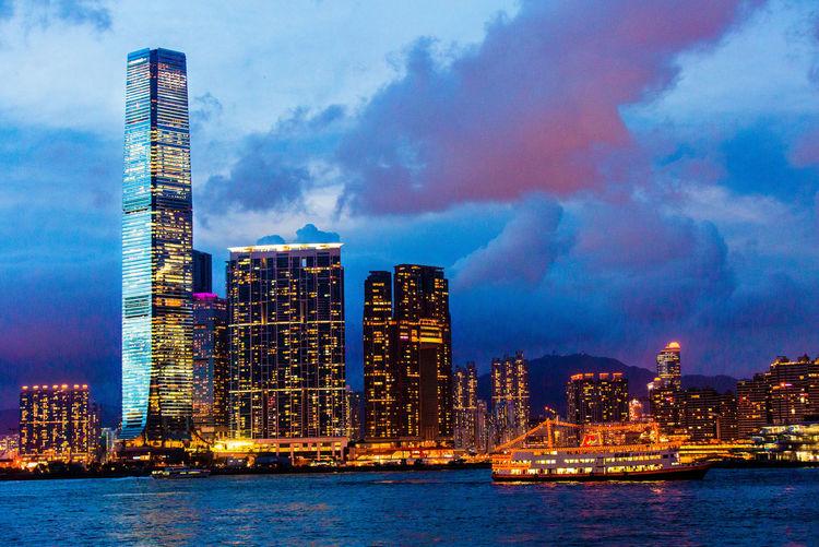 Illuminated city by sea against sky