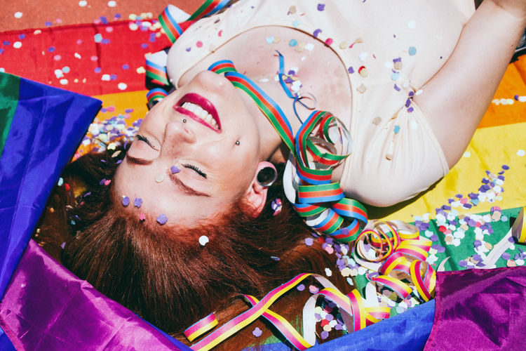 Young Woman Lying Down On Rainbow Flag During Sunny Day
