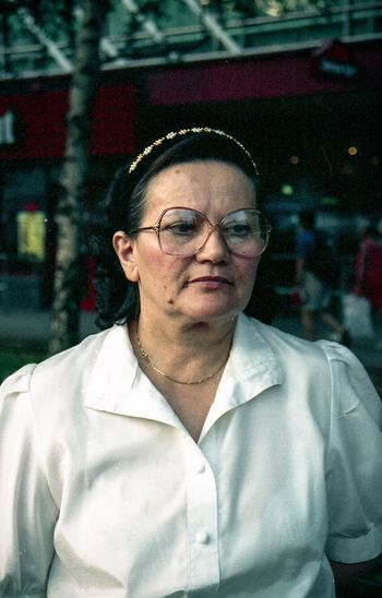 Portrait Of A Woman Portrait Grandmother Analogue Photography Glasses One Person Eyeglasses  Front View Portrait Headshot This Is Aging Leisure Activity Looking Outdoors City Young Adult Looking At Camera Waist Up Adult Architecture Lifestyles Real People Men